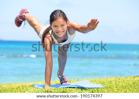 Woman fitness crossfit exercise training outdoors by the ocean sea. Beautiful fit female fitness girl model strength training on grass. Mixed race Asian female model - stock photo