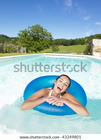 Woman floating in inner tube in pool and laughing. Vertical - stock photo