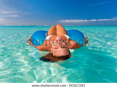 woman floats on blue tube in turquoise waters - stock photo