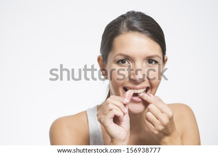 Woman flossing her teeth with dental floss to remove any food particles or bacteria caught between her teeth to prevent tooth decay or caries - stock photo