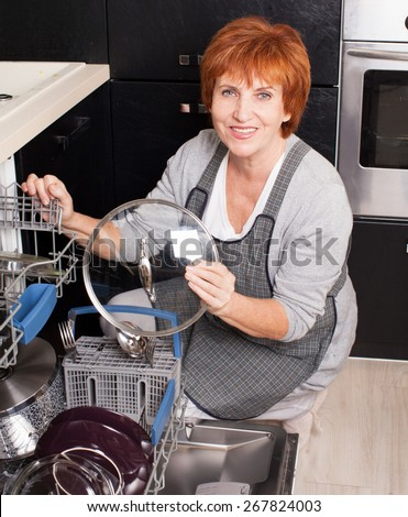 Woman folding the dishes in the dishwasher. Female at kitchen. Housework - stock photo