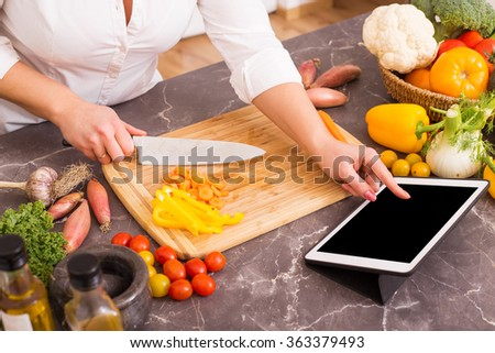 Woman following the recipe in tablet  - stock photo