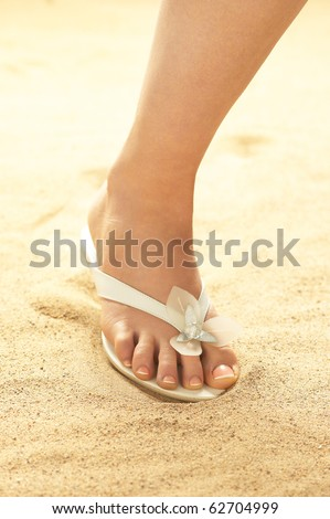 Woman foot on beach - stock photo