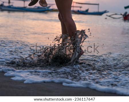 Woman foot on the beach splashing water - stock photo