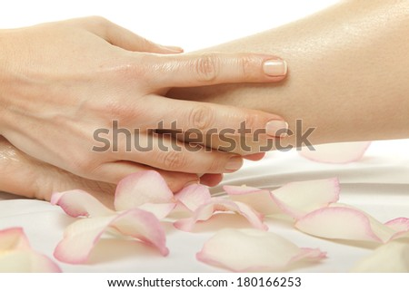 woman foot receiving gentle massage on bed with rose petals, isolated with work path  - stock photo