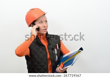 Woman foreman, head of construction is negotiating by mobile phone with a folder of documents in hand - stock photo