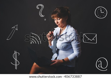 woman forty years of age European appearance holds hand glasses and looking at a laptop on a gray background, business ideas, social media - stock photo