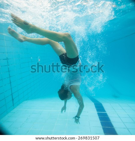Woman freediving underwater in a pool - stock photo