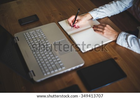 Woman freelancer female hands with pen writing on notebook at home or office - stock photo