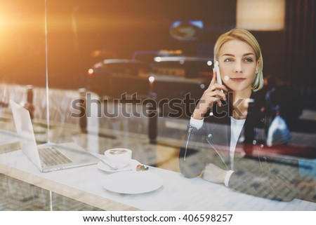 Woman freelancer is talking on mobile phone with her boyfriend, while is sitting in urban coffee shop at the table with open portable laptop computer, cup of cappuccino and dessert. Female student - stock photo
