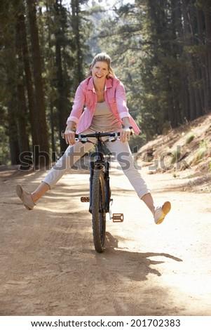 Woman freewheeling down country lane - stock photo