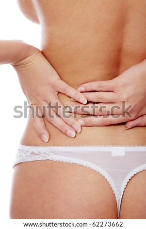Woman from behind, naked body, holding her back on the left side. Vertical. - stock photo