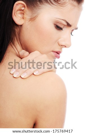 Woman from behind, naked body, holding her neck on the left side. Vertical.  - stock photo