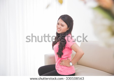 Woman frowning having stomachache sitting on the couch - stock photo