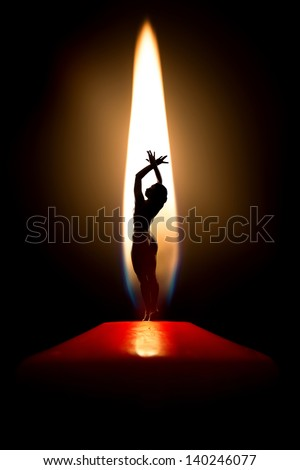 Woman fuse in a candle burning in a dark background - stock photo