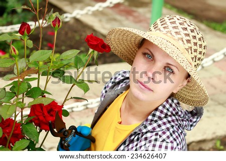 Woman gardening with roses in garden - stock photo