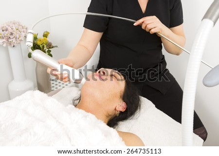 Woman get face treatment at beauty spa - stock photo