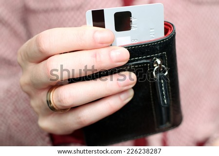 Woman get  out a credit card from  black purse in the shop - stock photo