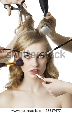 woman getting a beauty and hair style in the same time with hands making differente works, she is in front of the camera and looks up at right - stock photo