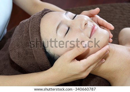Woman getting a facial massage - stock photo
