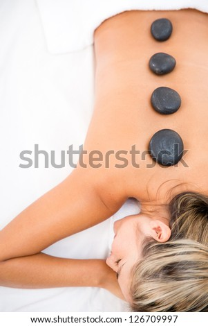 Woman getting a massage with hot stones - stock photo