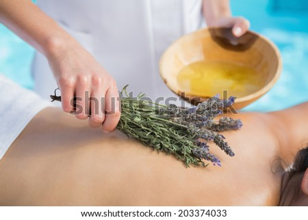 Woman getting an aromatherapy treatment poolside outside at the spa - stock photo