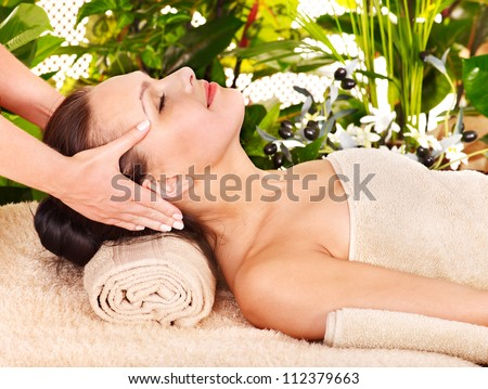 Woman getting facial massage in tropical beauty spa. - stock photo