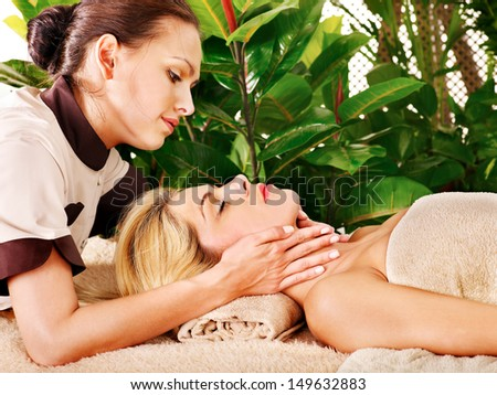 Woman getting facial massage in tropical spa. - stock photo