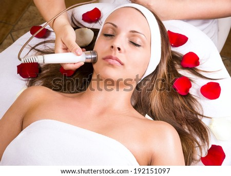 Woman getting laser and ultrasound face treatment in medical spa center, skin rejuvenation concept - stock photo