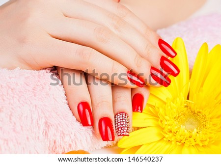 woman getting manicure for red nails in a beauty salon - stock photo