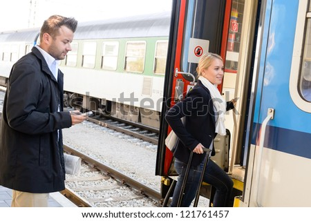 Woman getting on train man texting phone commuters journey stairs - stock photo