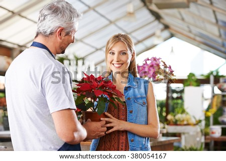 Woman getting service from gardener while shopping in a nursery - stock photo