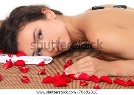 Woman getting spa treatment with black stone and rose petals - stock photo