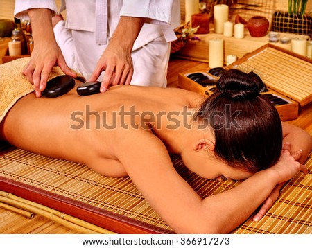 Woman getting stone therapy massage on bamboo floor spa.  - stock photo