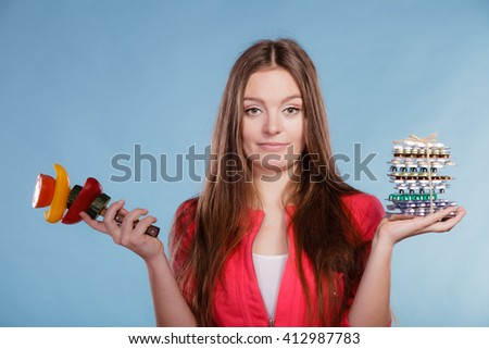 Woman girl holding diet weight loss tablets pills and vegetables. Choice between natural and synthetic way of slimming dieting. Health care. - stock photo