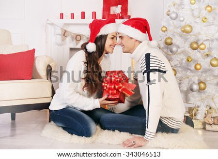 Woman gives a gift to the man in Christmas - stock photo
