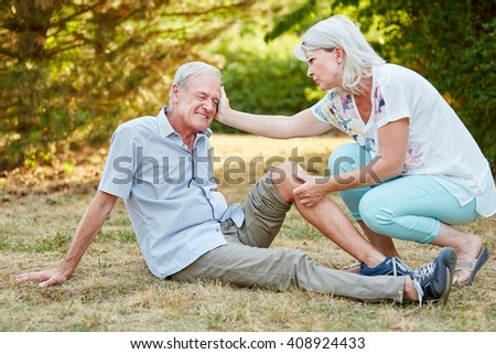Woman gives first aid to a man with a knee injury and comforts him - stock photo