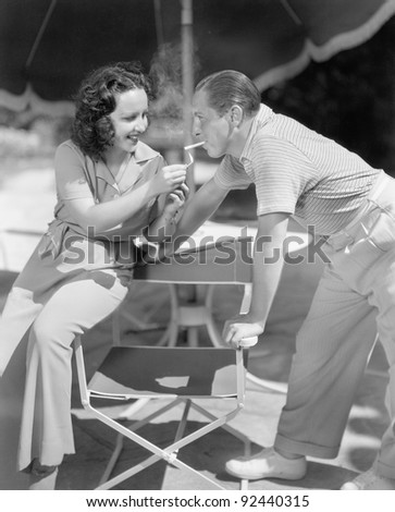 Woman giving a man a light for his cigarette - stock photo