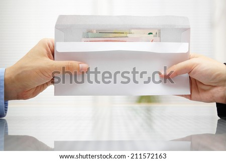 Woman giving envelope with money to Man - stock photo