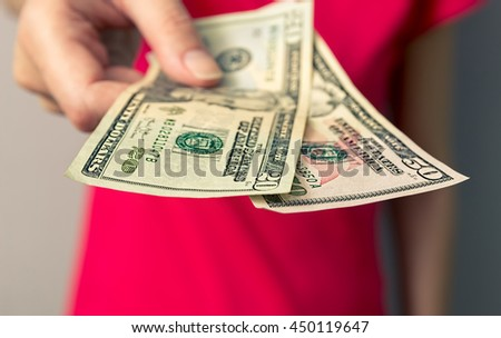 Woman giving money. Hand holding out cash. The red color in the background. - stock photo