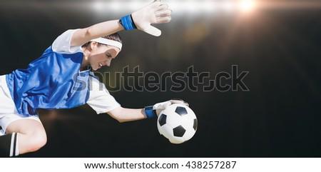 Woman goalkeeper stopping a goal against spotlight - stock photo