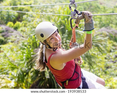 Woman going on a jungle zip line adventure - stock photo
