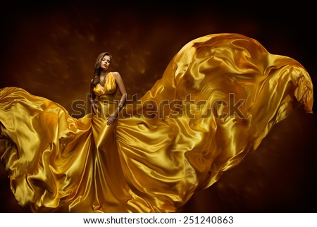 Woman Gold Dress, Lady In Fluttering Silk Gown, Fashion Beauty Model, Fabric Waving On Wind, Beautiful Girl With Long Dynamic Flying Cloth - stock photo
