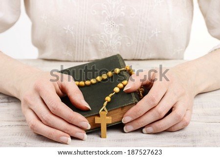 Woman golding wooden rosary and Holy Bible.  - stock photo