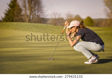 Woman golf player crouching and study the green before putting shot. - stock photo
