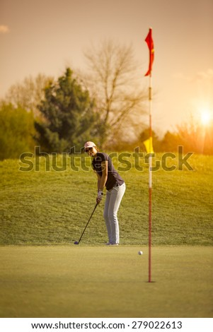 Woman golf player putting on green looking at flag, with sunset in background. - stock photo