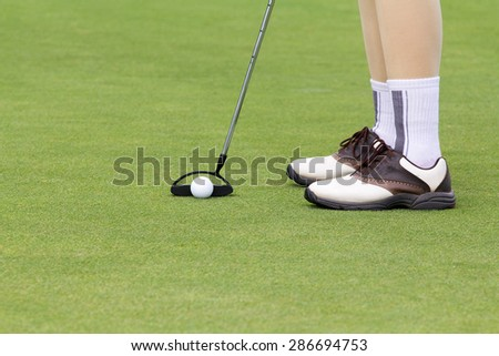 Woman golf player putting on the green - stock photo