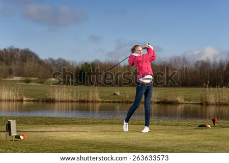 Woman golfer hitting a golf ball on the fairway with a club standing in the follow through position after the stroke in front of a pond or water hazard on a rural golf course - stock photo