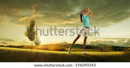 Woman golfer hitting the ball on the background scenery  beautiful - stock photo
