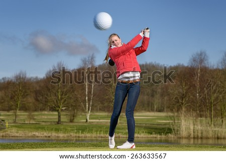 Woman golfer hitting the golf ball with a driver in front of a water hazard on a golf course with the ball flying through the air towards the camera - stock photo